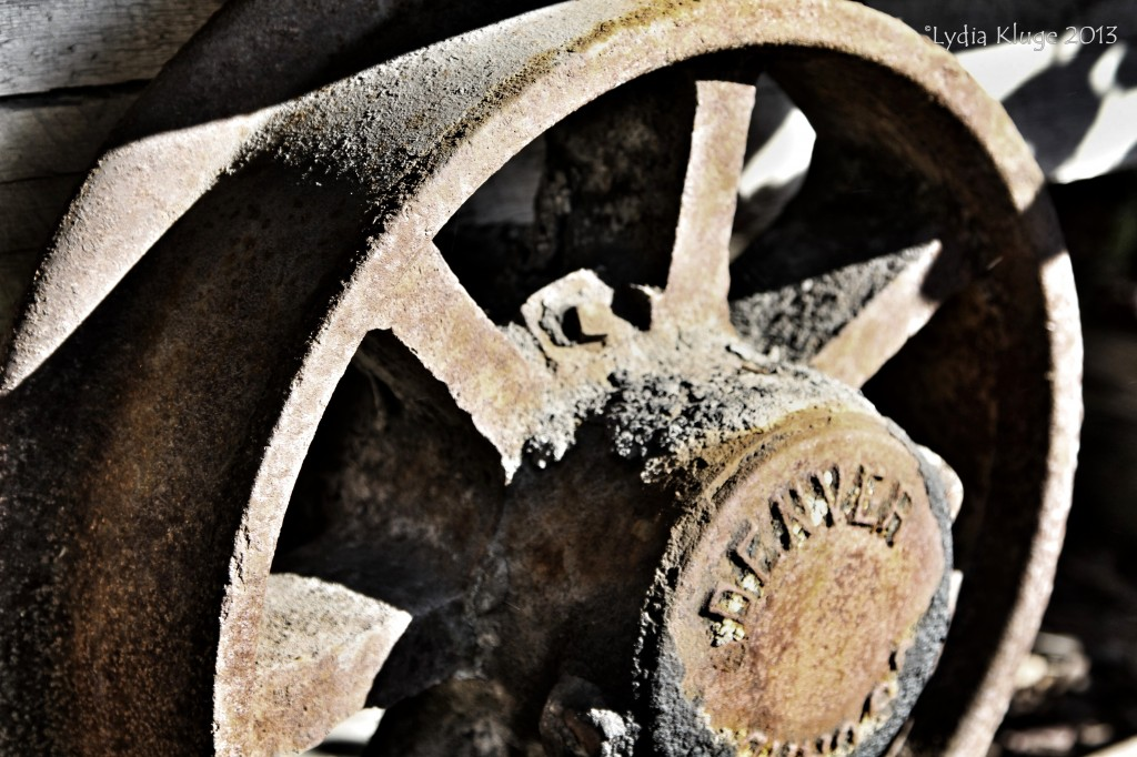 The rusty wheel of a disused mine cart.