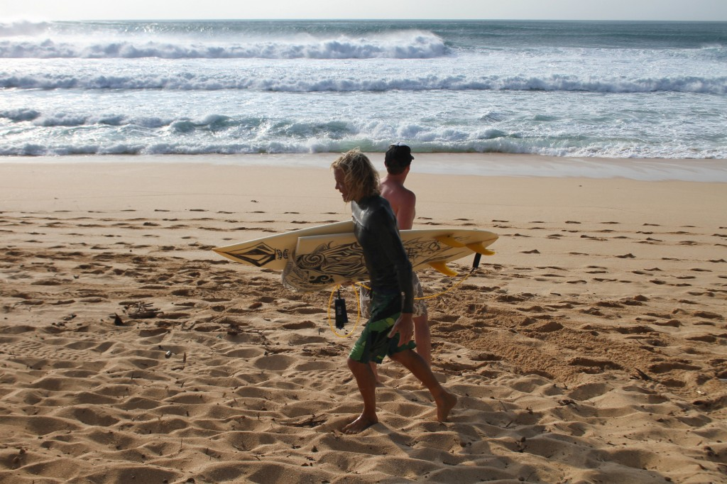 Team Volcom Pro Surfer Gavin Beschen comes in from riding Banzai Pipeline, happy but with a broken board.